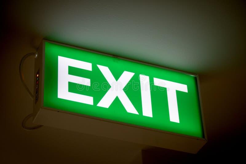 Ciérrese encima de muestra verde de la salida en puerta en el edificio fotos de archivo