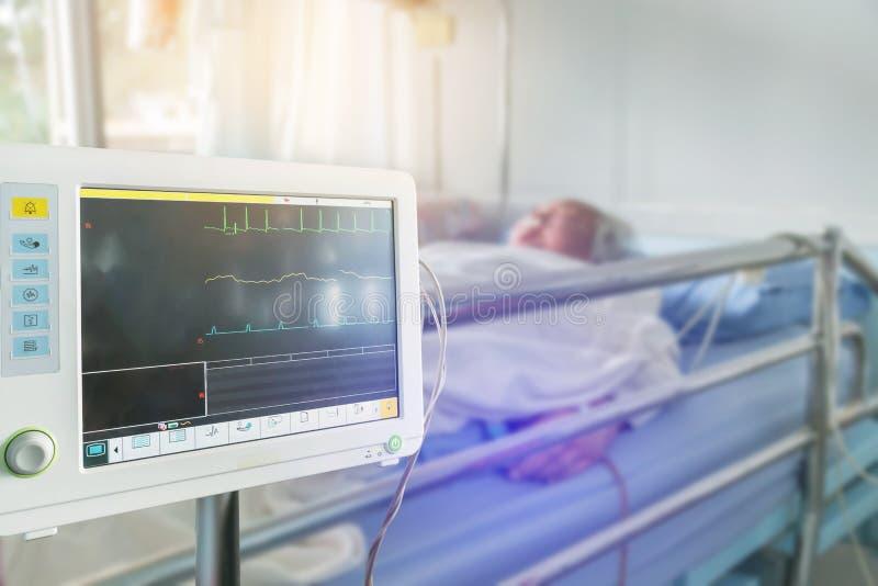 Ciérrese encima de muestras vitales digitales del monitor del corazón de medición y de la presión arterial con sueño paciente may foto de archivo