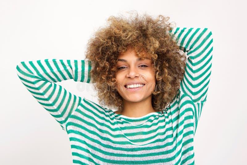 Ciérrese encima de mujer afroamericana joven sonriente con las manos en pelo contra el fondo blanco fotografía de archivo libre de regalías