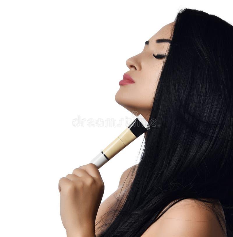 Ciérrese encima de mujer desnuda en morenita del perfil con los ojos cerrados que sostienen un pequeño tubo de la crema en blanco imágenes de archivo libres de regalías