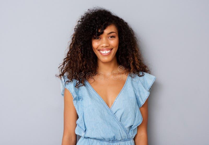 Ciérrese encima de mujer negra de g de los jóvenes hermosos contra fondo gris imagen de archivo libre de regalías