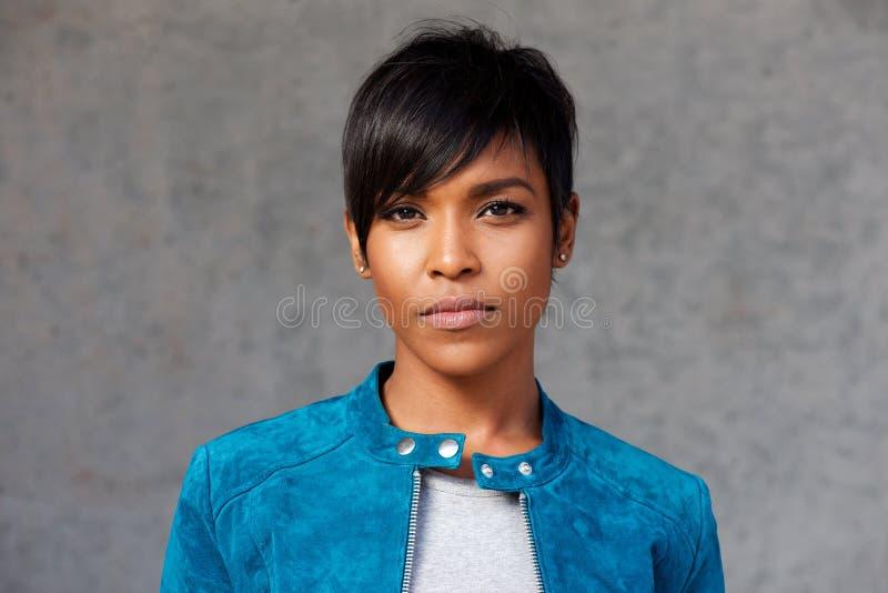 Ciérrese encima de mujer negra joven de moda con la chaqueta azul fotos de archivo