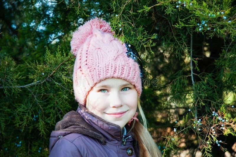 Ciérrese encima de niña del retrato en invierno con la picea fotografía de archivo