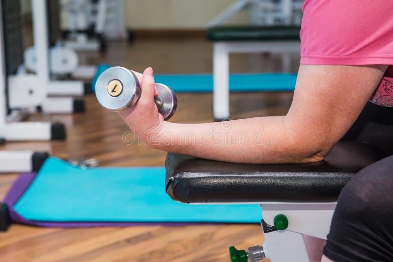 Ciérrese encima de ninguna mujer mayor de la cara que hace los ejercicios especiales activos, trabajando con los pesos en gimnasi imagen de archivo libre de regalías