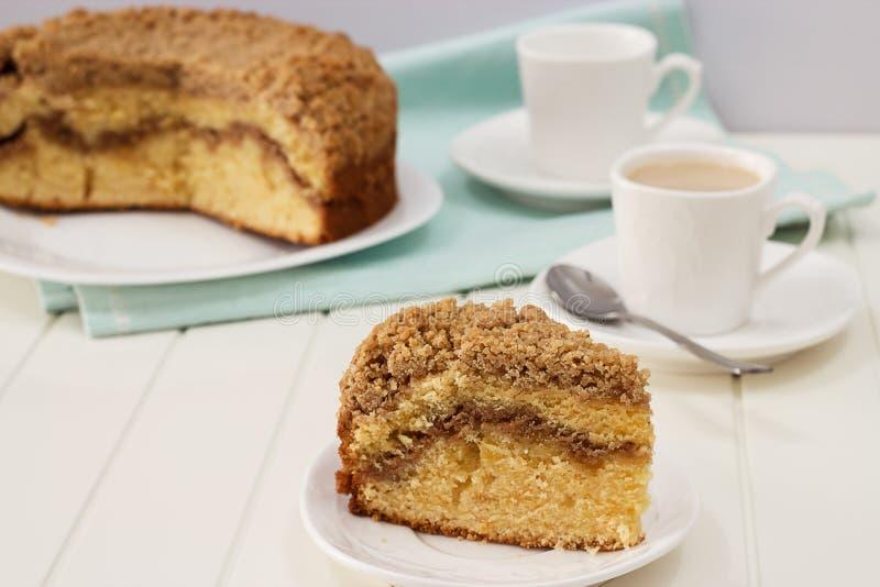 Ciérrese encima de pedazo de torta de café de la migaja del canela y de taza hechas en casa de té de la leche imagenes de archivo