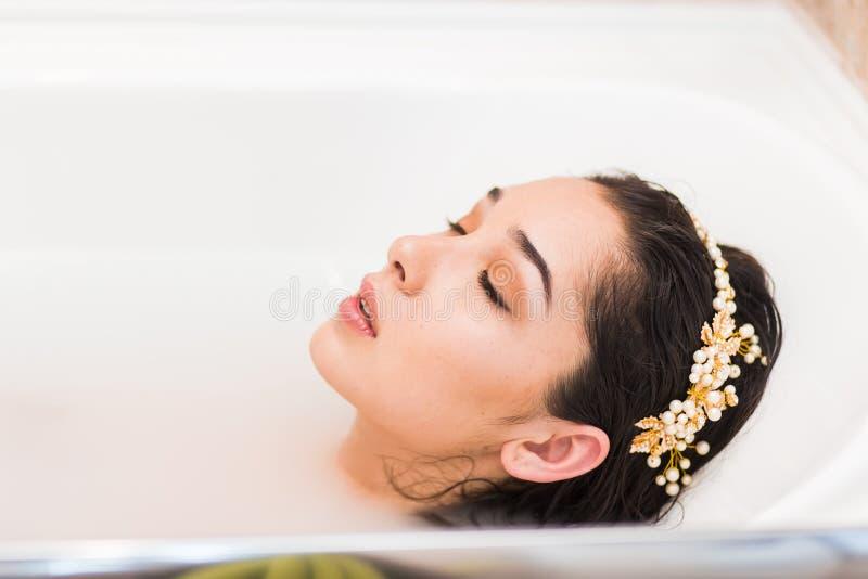 Ciérrese encima de perfil de la cara de la mujer con la decoración en la cabeza que miente en un baño foto de archivo