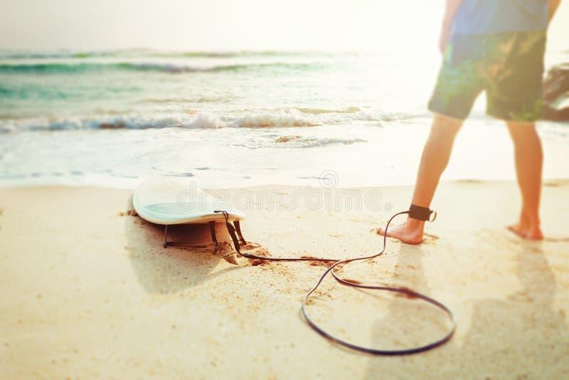 Ciérrese encima de pies de la persona que practica surf de sexo masculino, que se coloca en la playa del mar o del océano y estud imagen de archivo libre de regalías