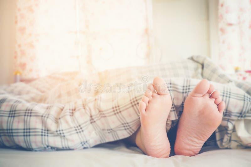 Ciérrese encima de pies de mujeres que duermen en cama por mañana imagenes de archivo