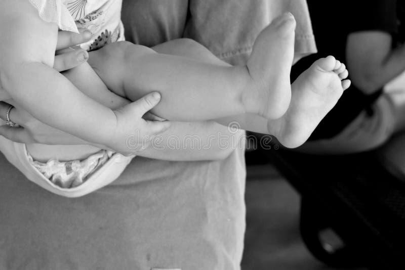 Ciérrese encima de pies y de dedos del pie de las piernas del bebé imagenes de archivo