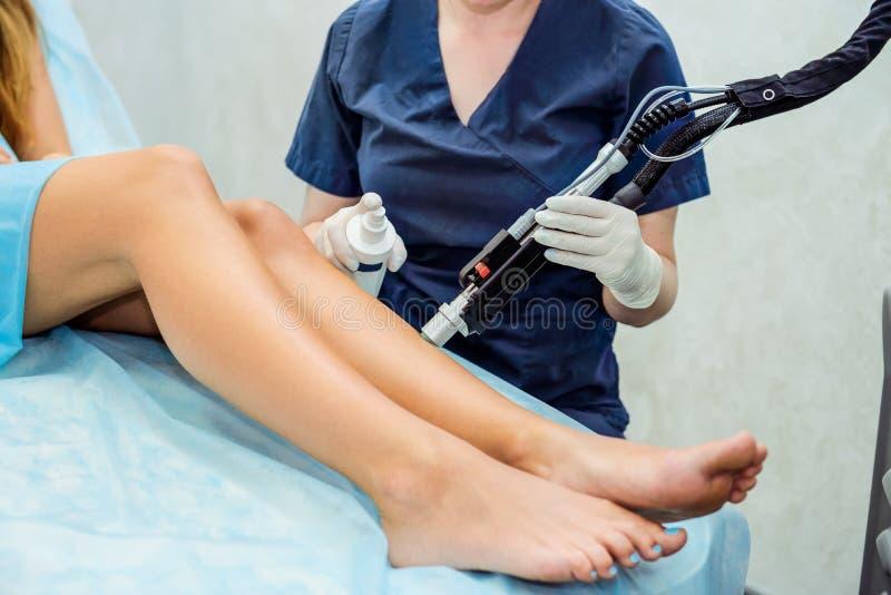 Ciérrese encima de retiro del pelo del laser en el salón de belleza Mujer que tiene epilation de las piernas Equipo del retiro de fotos de archivo