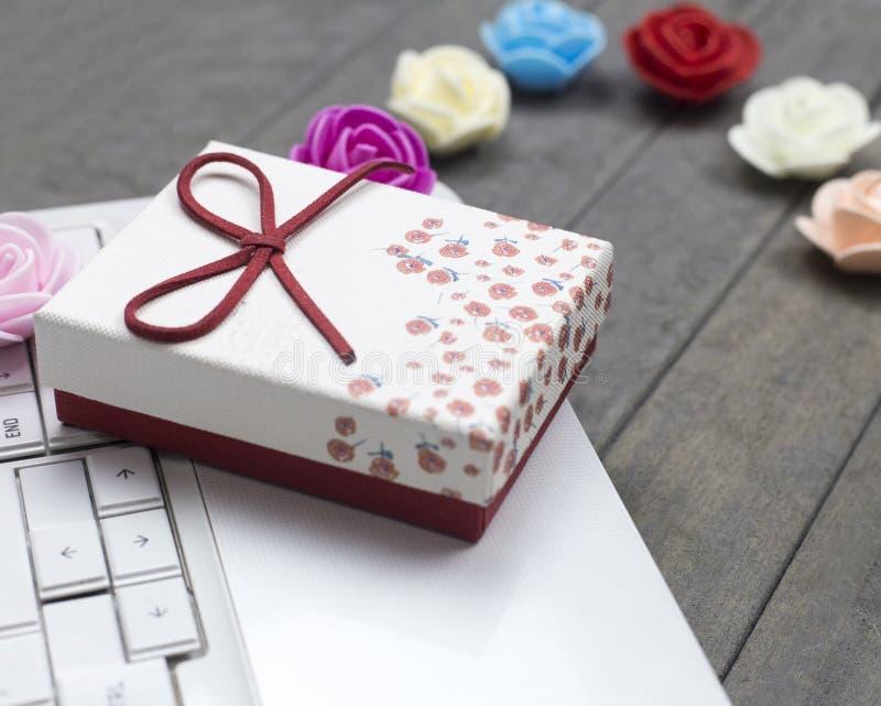 Ciérrese encima de rosas, del ordenador portátil blanco y de la caja de regalo roja en fondo fotografía de archivo