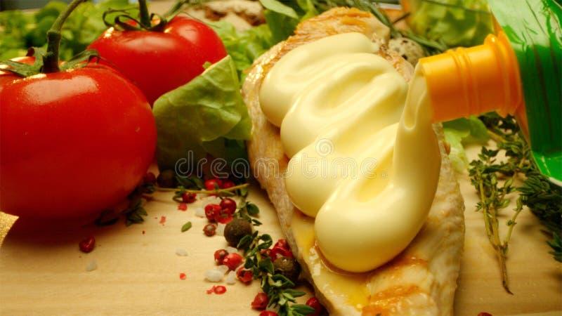 Ciérrese encima de tiro comercial de la pechuga de pollo asada a la parrilla deliciosa cubierta con mayonesa con verdes frescos y imagen de archivo