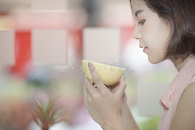 Ciérrese encima de tiro de la hembra asiática hermosa joven que sostiene la taza amarilla imagen de archivo