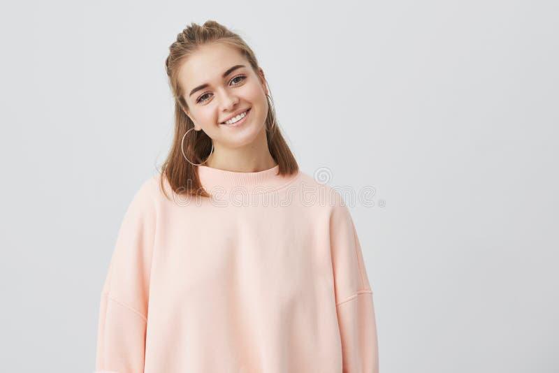 Ciérrese encima de tiro de la hembra caucásica encantadora con el pelo recto justo vestido en rosa, suavemente mirando la cámara, fotos de archivo libres de regalías