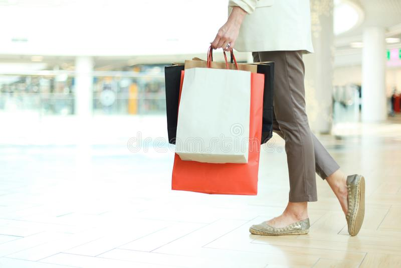 Ciérrese encima de tiro de la pierna de la mujer joven que lleva los panieres coloridos mientras que camina en alameda de compras fotografía de archivo libre de regalías