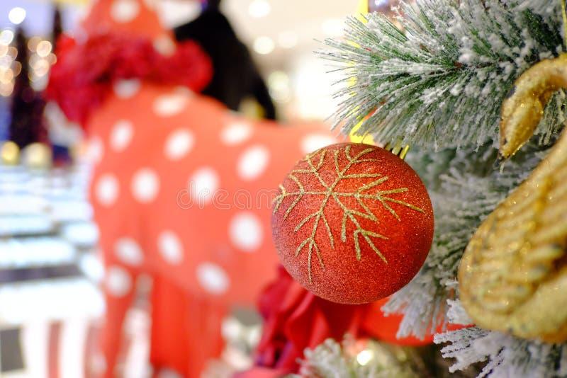 Ciérrese encima de un ornamento rojo hermoso de la bola que cuelga de un árbol de navidad foto de archivo