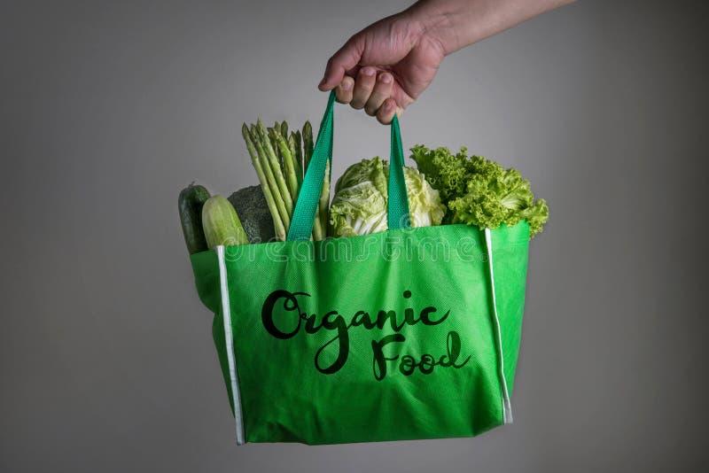 Ciérrese encima de una mano que sostiene el bolso de ultramarinos verde con el texto del alimento biológico imágenes de archivo libres de regalías