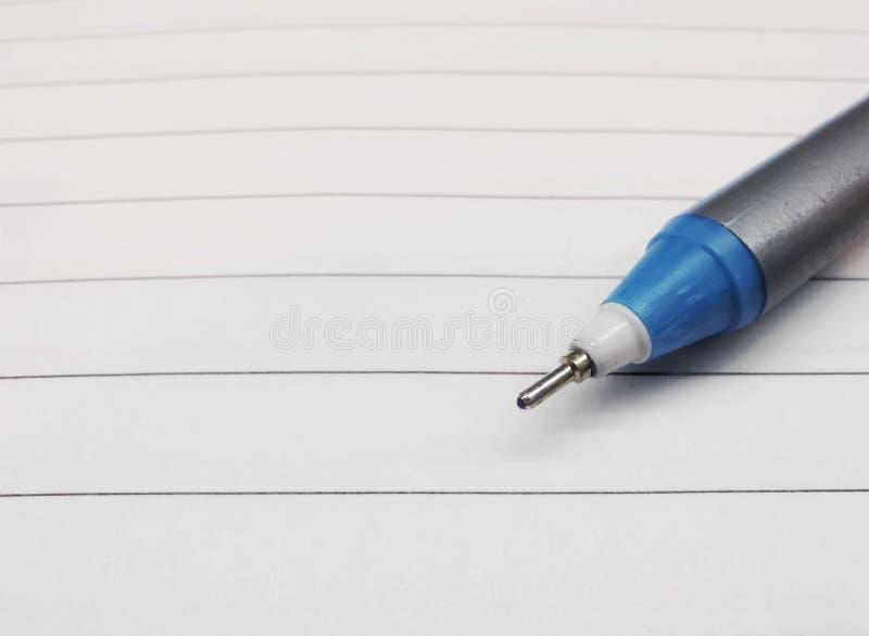 Ciérrese encima de una pluma en el papel con las líneas fondo imagen de archivo