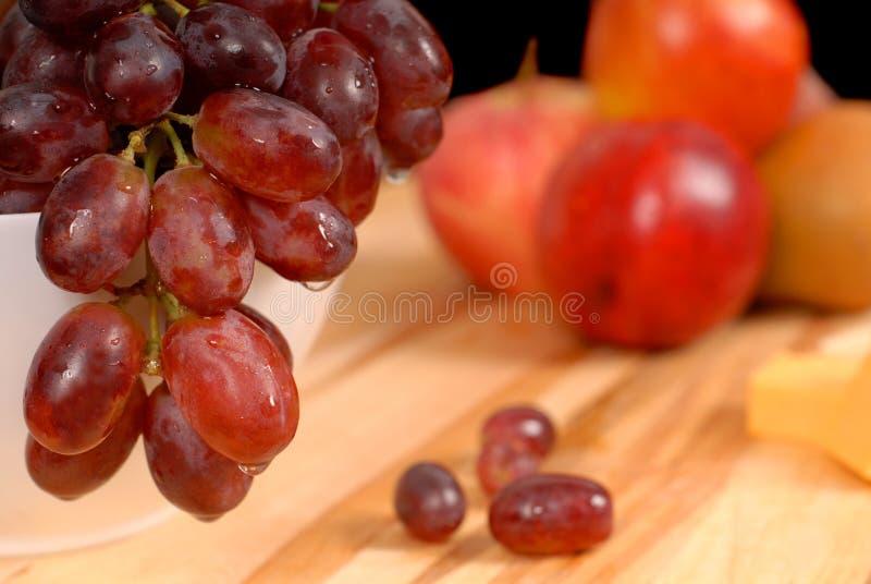 Ciérrese encima de vista de la fruta y del queso deliciosos en la tarjeta de corte fotos de archivo libres de regalías