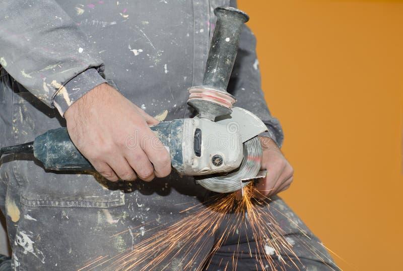 Ciérrese encima de vista de las manos de un trabajador usando una sierra radial fotografía de archivo