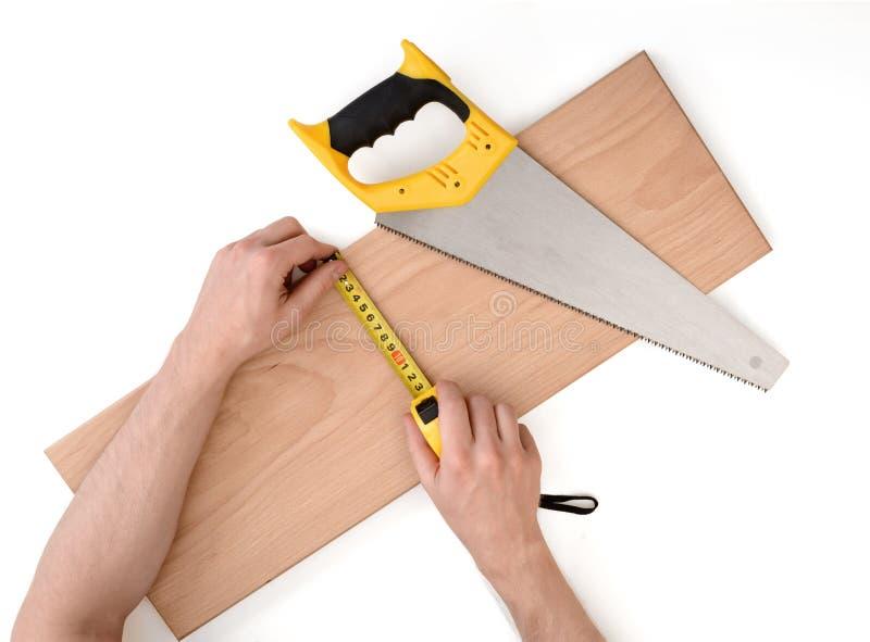 Ciérrese encima de vista de un man& x27; s da el tablón de madera de medición con la línea de la cinta, aislada en el fondo blanc fotografía de archivo libre de regalías