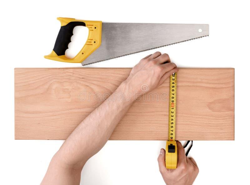 Ciérrese encima de vista de un man& x27; s da el tablón de madera de medición con la línea de la cinta, aislada en el fondo blanc foto de archivo
