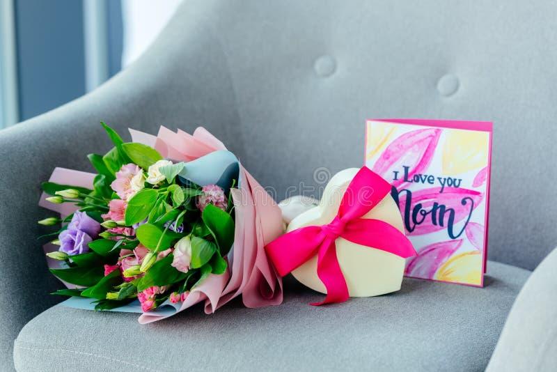 ciérrese encima de vista del ramo envuelto de flores, de regalo en forma de corazón y te quiero de postal de la mamá en la butaca fotos de archivo