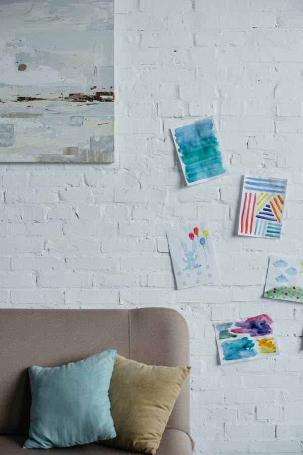 ciérrese encima de vista del sitio infantil vacío con el sofá y los dibujos coloridos imagenes de archivo