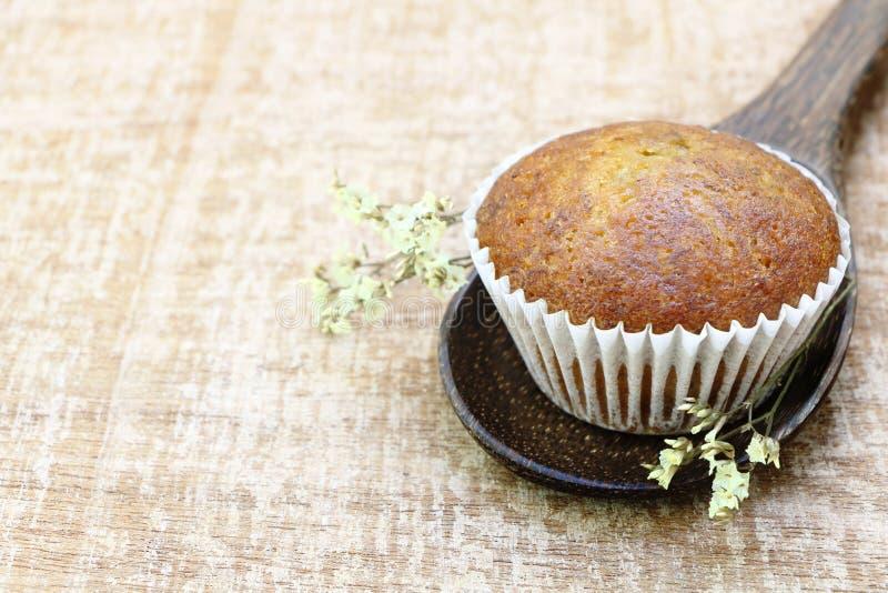 Ciérrese encima de vista lateral de la sola del plátano de la taza panadería de la torta sobre la mirada de madera de la cucharón imagen de archivo