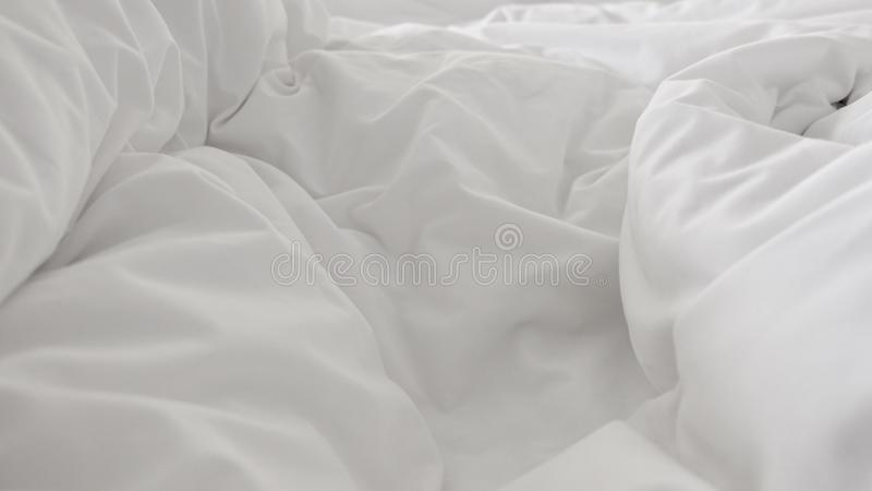 Ciérrese encima de vista superior de la almohada blanca en cama y con la manta sucia de la arruga en dormitorio foto de archivo