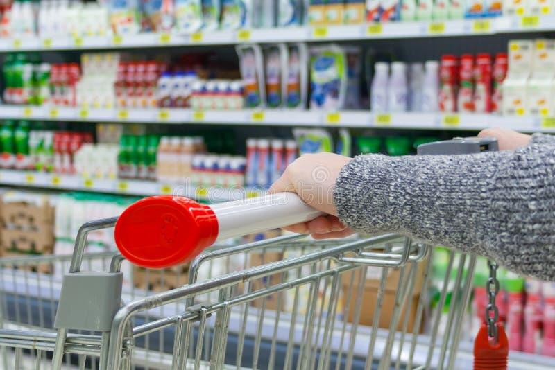 Ciérrese encima de vista de una mano femenina con la carretilla de mano en supermercado imagen de archivo libre de regalías