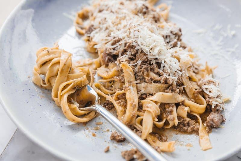 Ciérrese encima de Wagyu Ragu con el desmoche de las pastas de los tallarines con el queso cheddar Espaguetis rodados con la bifu foto de archivo