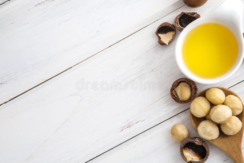 Ciérrese encima del aceite de almendra en la semilla de la botella y de la almendra en la taza blanca para el masaje del aceite y fotografía de archivo