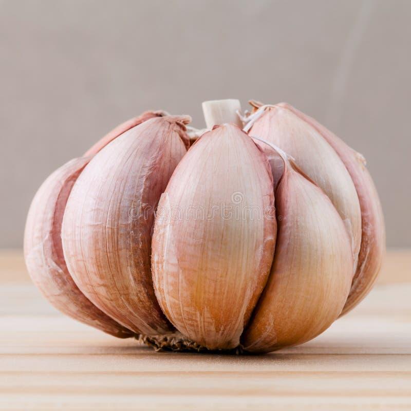 Ciérrese encima del ajo orgánico con el foco selectivo en los vagos de madera de la teca imágenes de archivo libres de regalías
