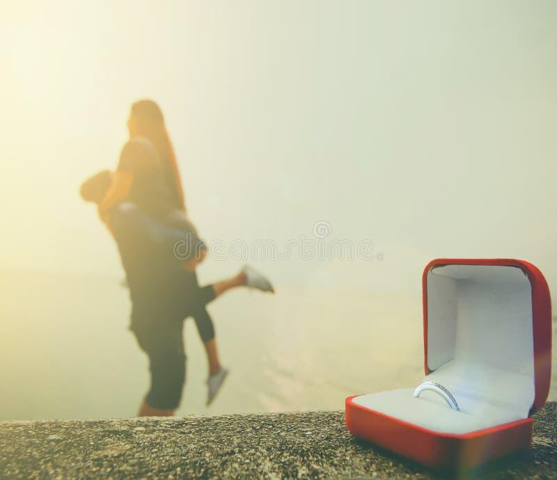 Ciérrese encima del anillo de bodas en caja roja con el extracto borroso del lazo humano foto de archivo