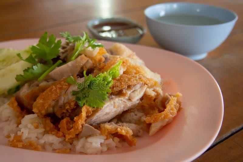 Ciérrese encima del arroz del Freír-pollo en una placa y asperje con coriandro Con caldo de pollo y una taza de salsa de inmersió foto de archivo