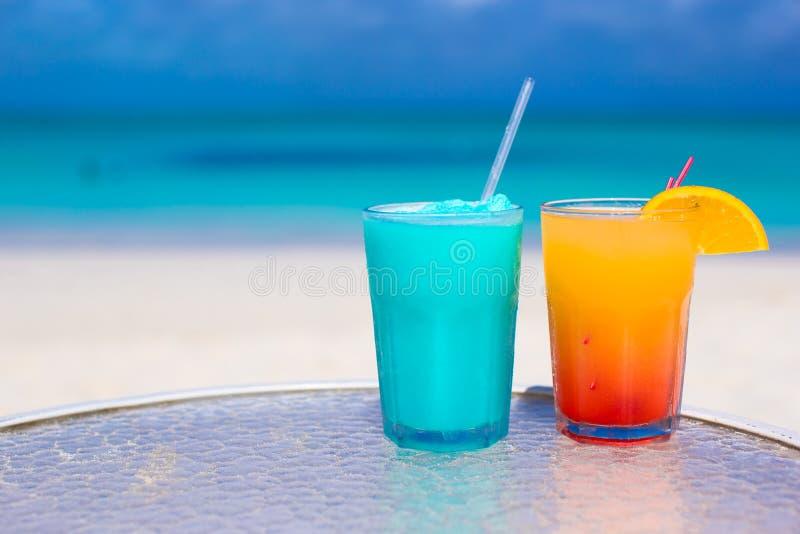 Ciérrese encima del cóctel azul de Curaçao y del mango en la playa arenosa blanca fotos de archivo
