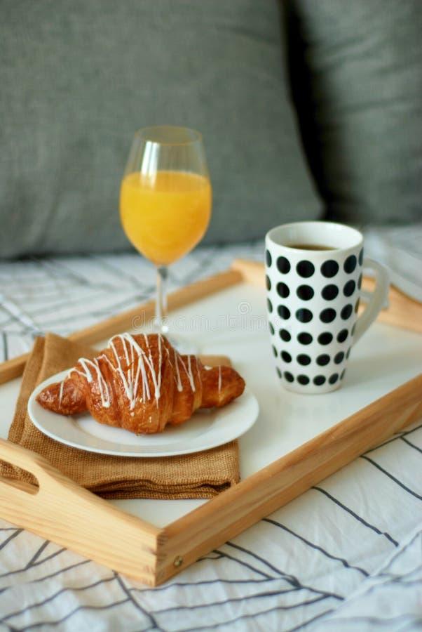 ciérrese encima del desayuno en cama Comida blanca del café y del chocolate de los cruasanes Taza de coffe o de té Luz de la maña imágenes de archivo libres de regalías