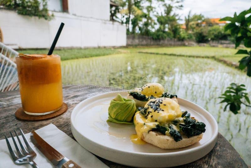 Ciérrese encima del desayuno sano con la tostada del pan y el huevo escalfado con la espinaca, aguacate en la tabla de madera con imagen de archivo