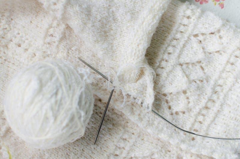 Ciérrese encima del detalle de la textura y del ovillo tejidos las lanas blancas del diseño del suéter del bebé del punto de la a foto de archivo