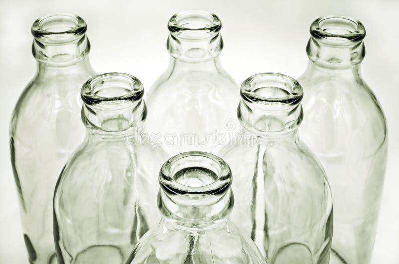 Ciérrese encima del detalle de las botellas de cristal en el fondo blanco imagen de archivo