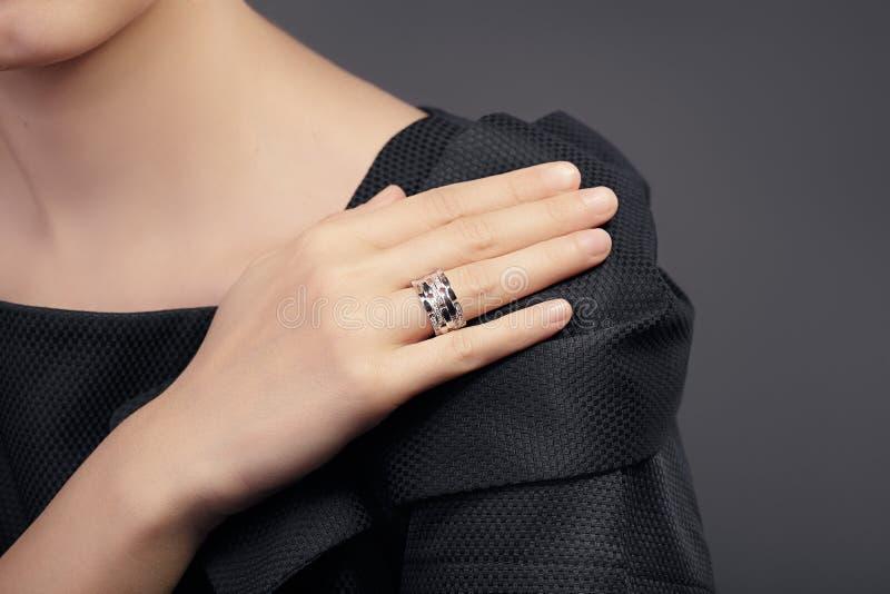 Ciérrese encima del detalle de un anillo en un modelo femenino de la mano imagenes de archivo