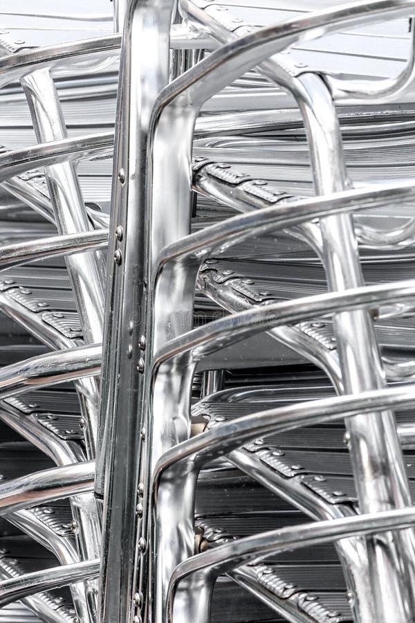 Ciérrese encima del detalle de una pila de sillas de aluminio de plata fotografía de archivo