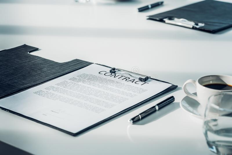 Ciérrese encima del documento del contrato del negocio sobre la tabla de la sala de reunión con la pluma fotografía de archivo