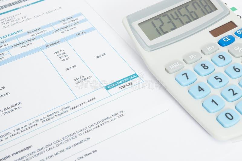 Ciérrese encima del estudio tirado de factura de servicios públicos y de la calculadora sin pagar sobre ella foto de archivo
