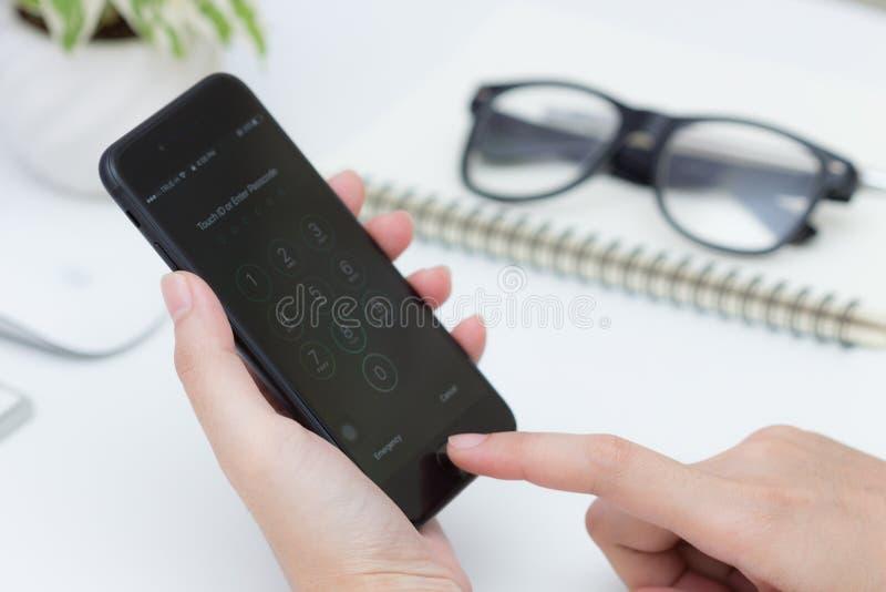 Ciérrese encima del finger scaning de la mano de la mujer para desbloquear el iphone 7 imágenes de archivo libres de regalías