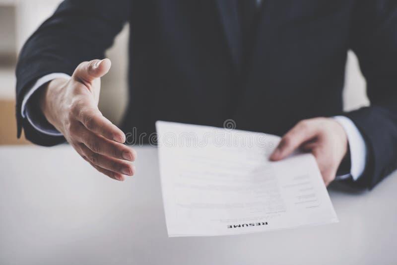 Ciérrese encima del hombre de negocios joven Taking Resume en oficina fotografía de archivo