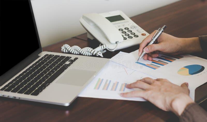 Ciérrese encima del hombre de negocios que analiza el documento del gráfico con el ordenador portátil y el teléfono imagen de archivo libre de regalías