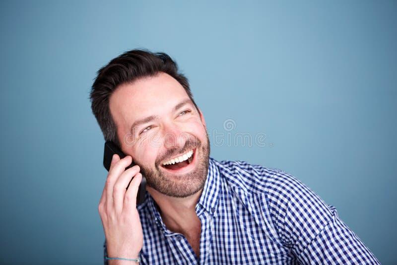 Ciérrese encima del hombre feliz que habla en el teléfono móvil y la risa fotografía de archivo