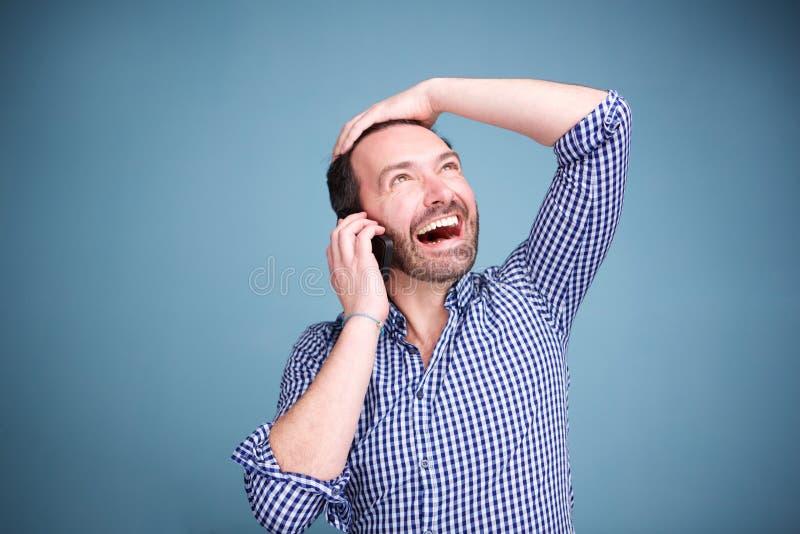 Ciérrese encima del hombre feliz que habla en el teléfono móvil y que mira para arriba foto de archivo